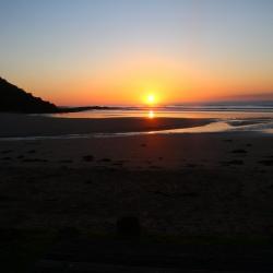 Strand und Meer und Sonnenuntergang